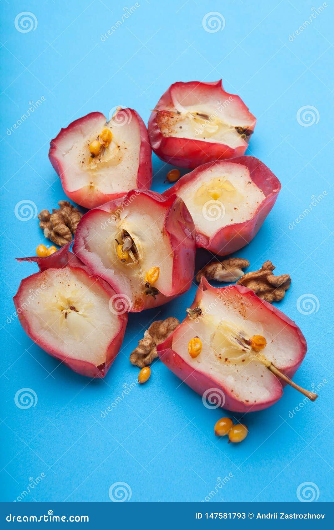 Alimento sano per perdita di peso dalle mele al forno rosse con i dadi e l aceto su un fondo blu, verticalmente