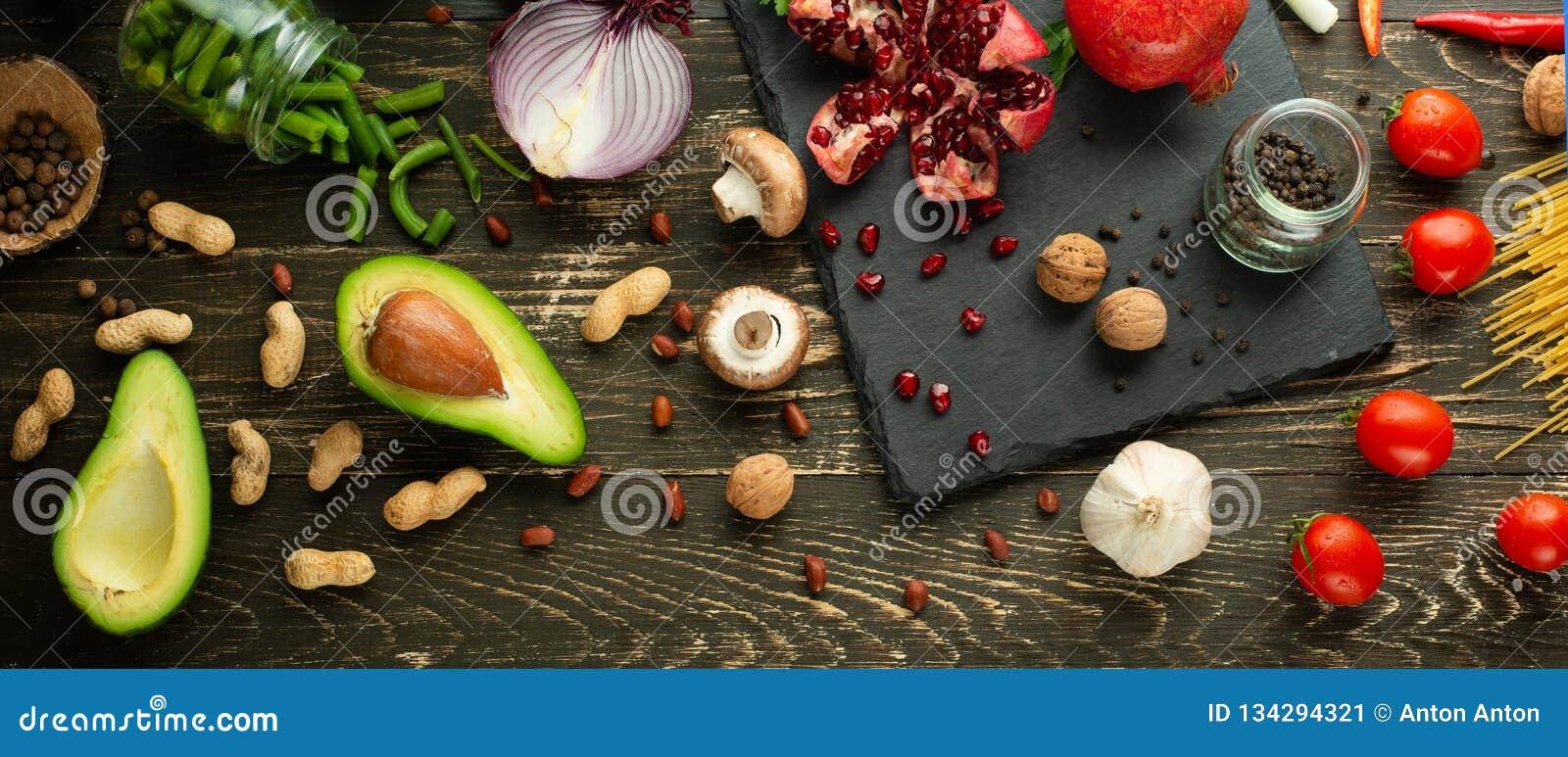 Alimento saudável do vegetariano que cozinha ingredientes Vegetais colocados lisos, frutos, abacates, porcas, cogumelos, cebolas,