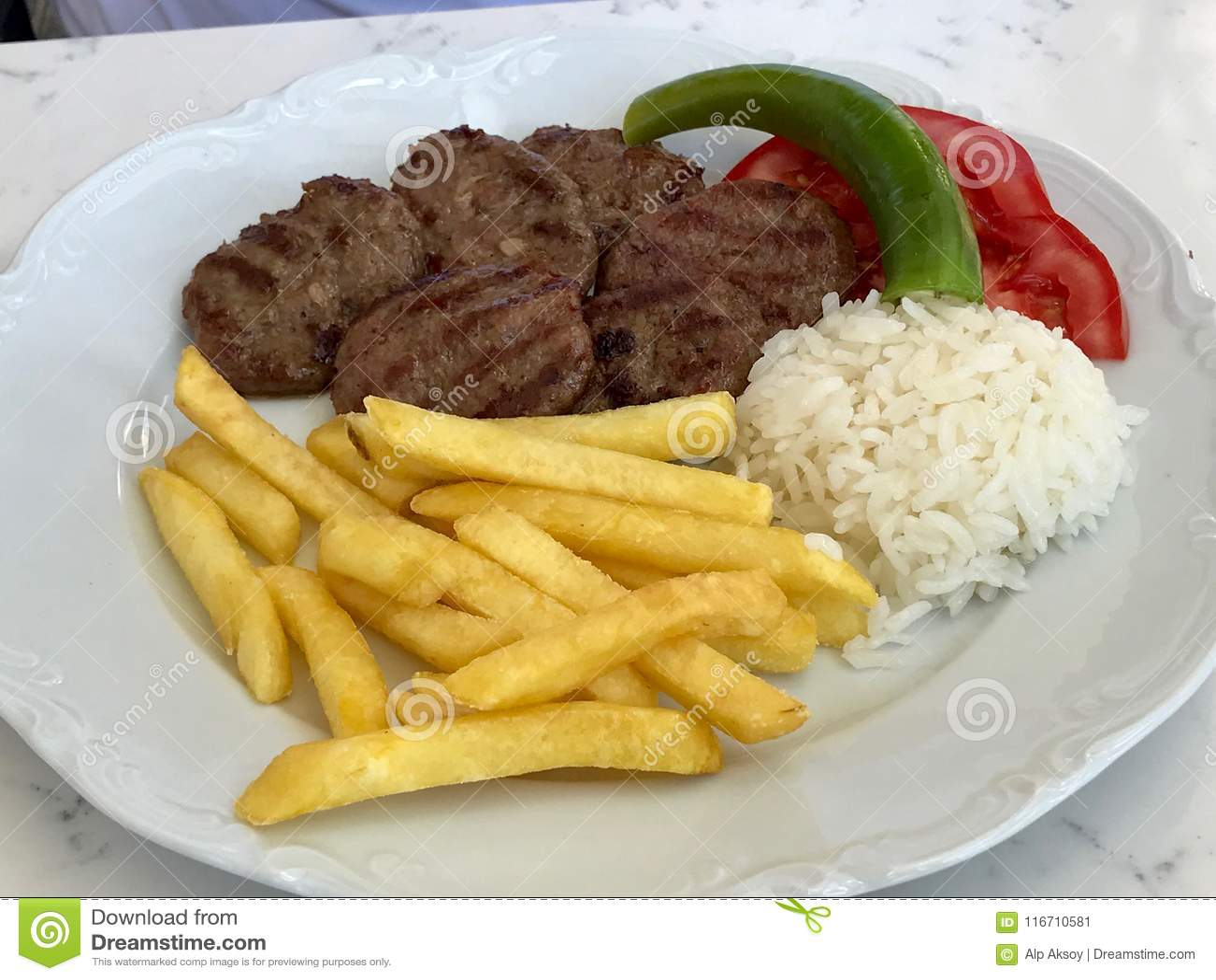 Alimento turco Kofte ou Kofta/pilha de almôndegas com arroz Pilav/pilau e batatas
