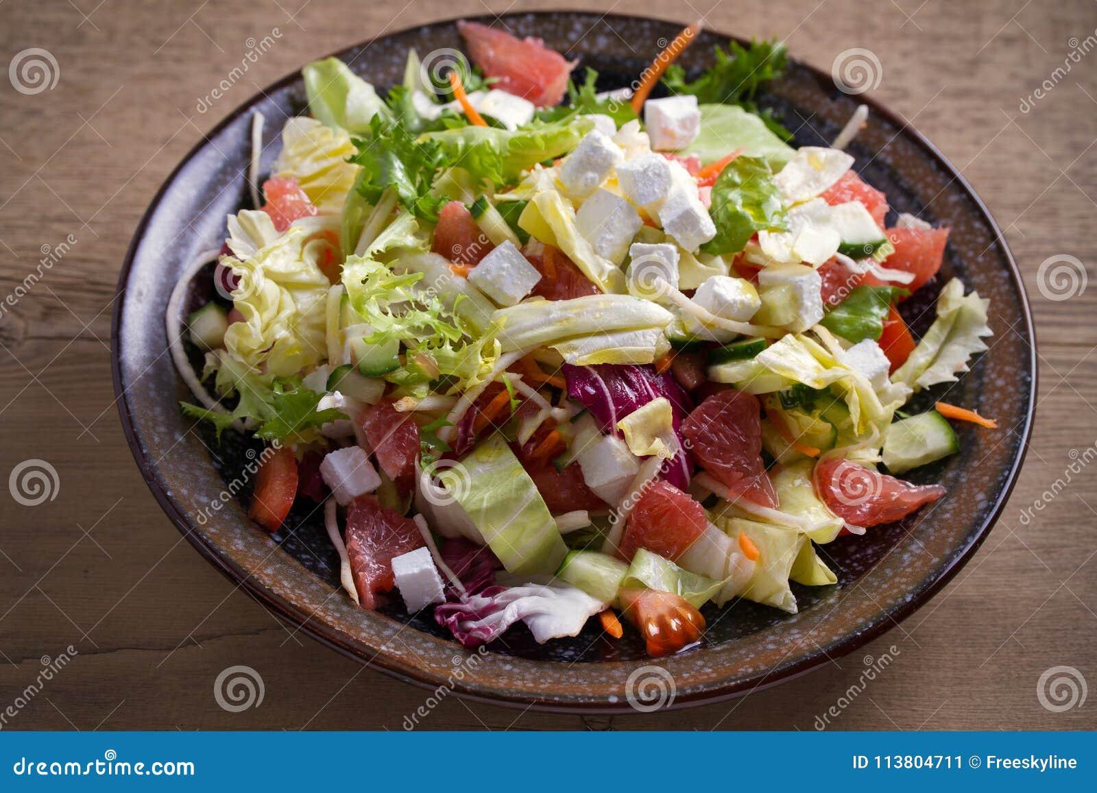 Alimento vegetariano sano: insalata del pompelmo, del pomodoro, della lattuga e del cetriolo dell agrume con feta in ciotola sull