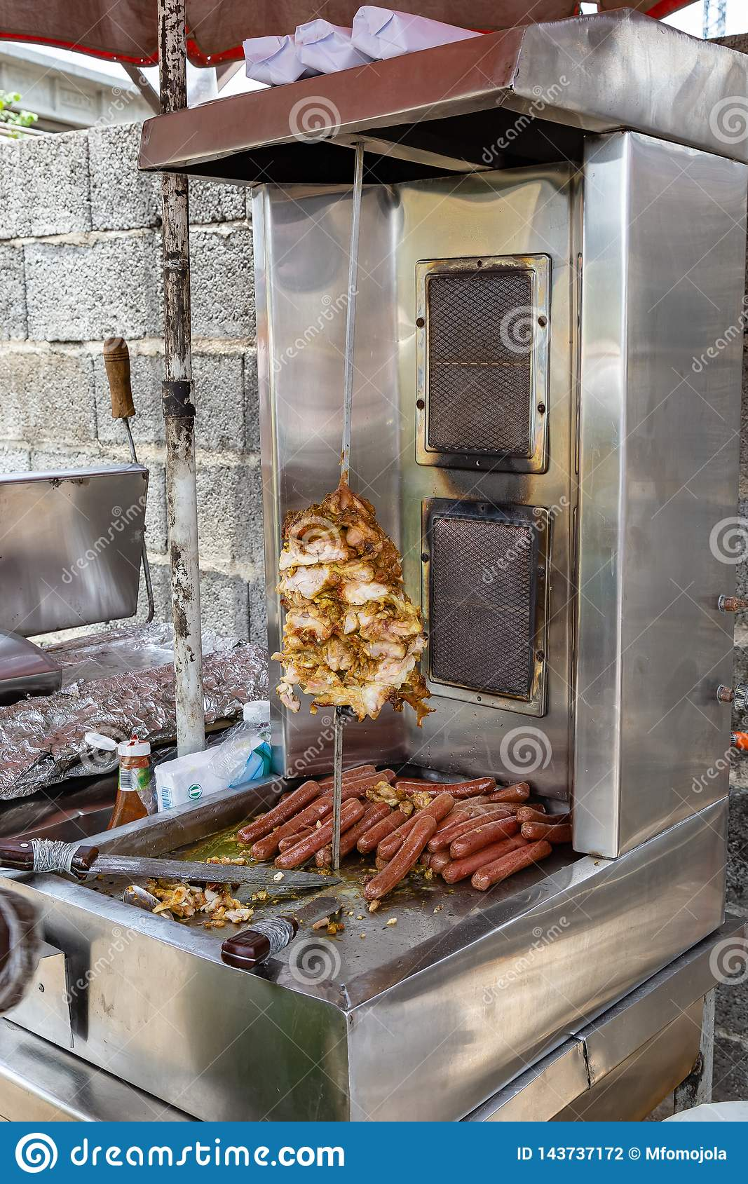 Alimentos da rua em Lagos Nigéria; shawarma da galinha, carne do giroscópio e cachorros quentes