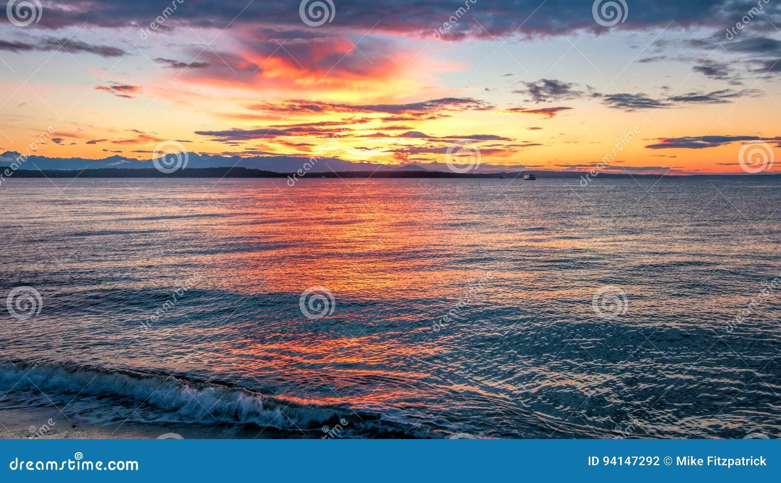 Alki Beach Sunset med Silhouetted olympiskt område och vattenreflexioner n