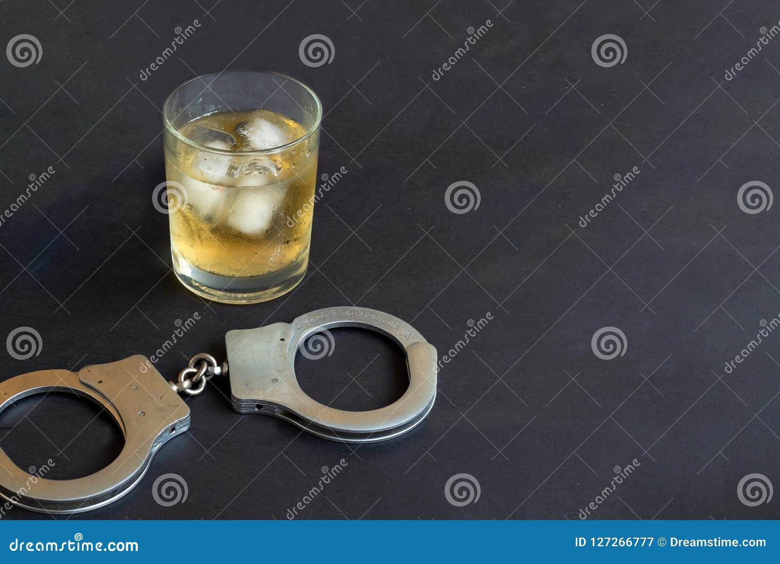 Alkohol und Handschellen auf schwarzem Farbhintergrund