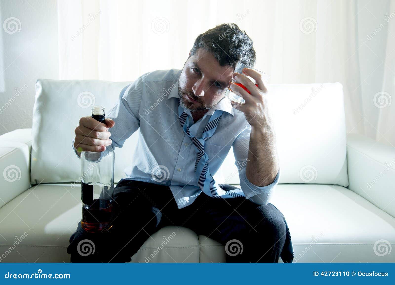 Alkoholiczny Biznesowy mężczyzna jest ubranym błękitnego luźnego krawat pijącego z whisky butelką na leżance