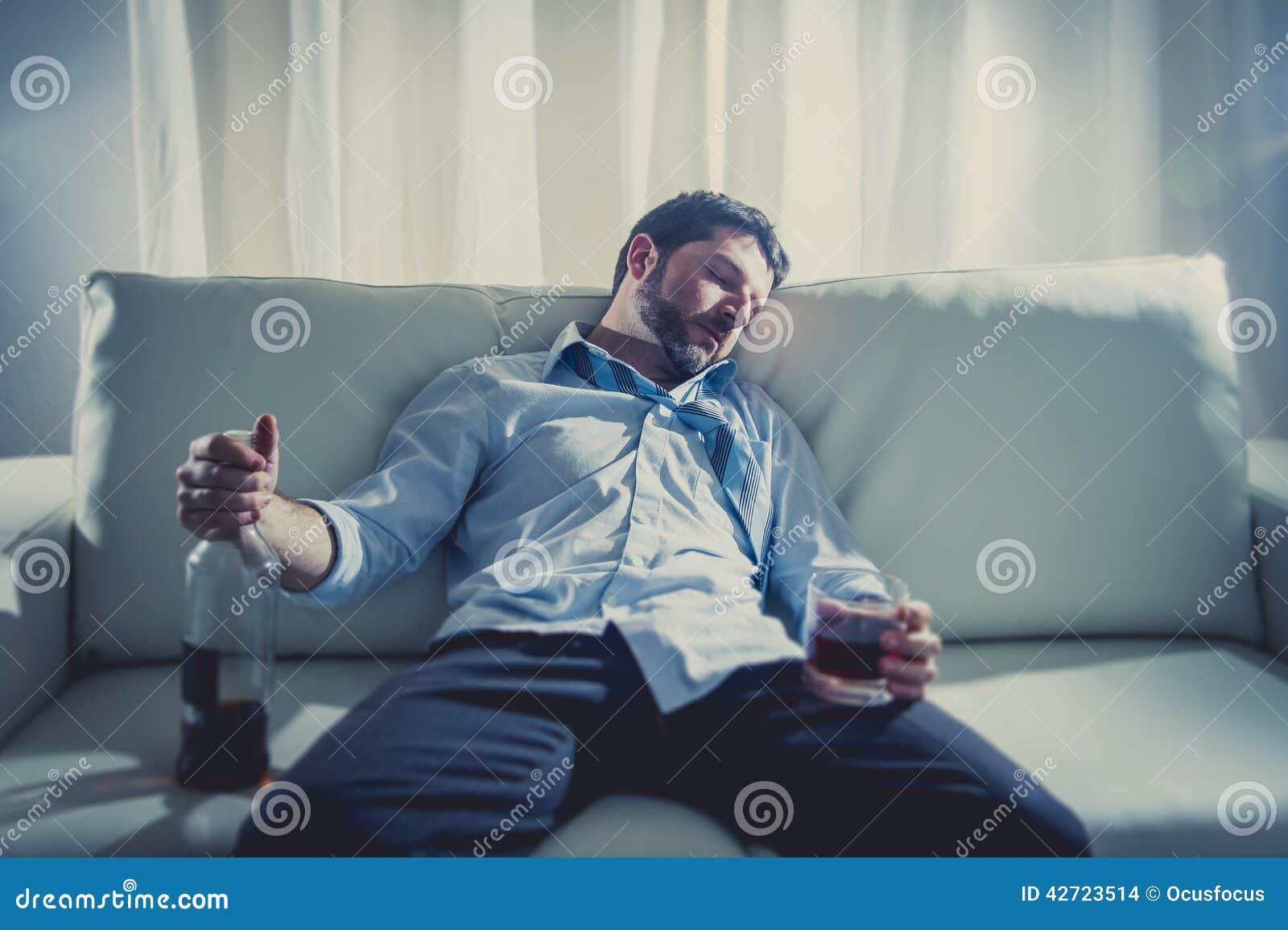 Alkoholiczny Biznesowy mężczyzna w błękitnym luźnym krawata dosypianiu pijącym z whisky butelką na leżance