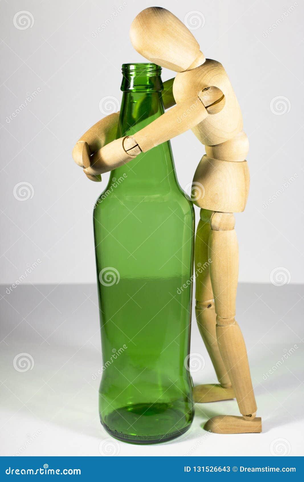 Alkoholizm, alkoholu nałóg, ogólnospołeczny problem: drewniana atrapa, osamotniony opój, alkoholiczka, ściska butelkę piwo