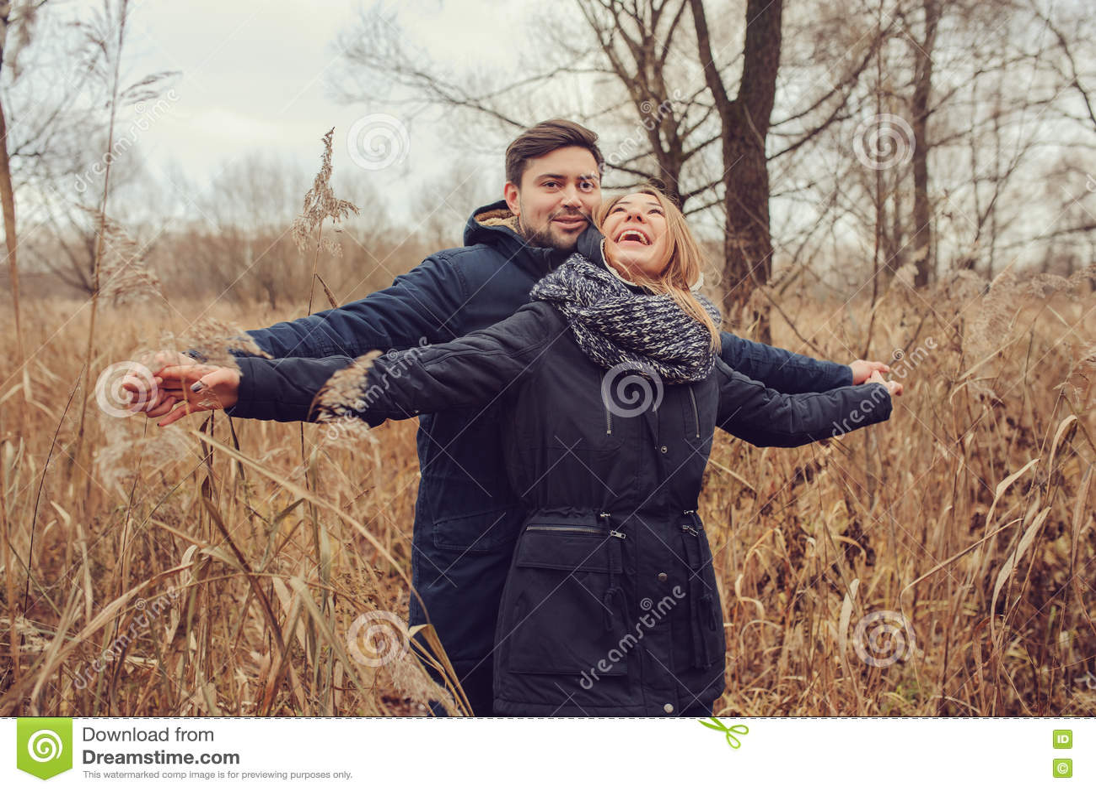 All aperto felici delle giovani coppie amorose su accogliente riscaldano insieme la passeggiata nella foresta di autunno