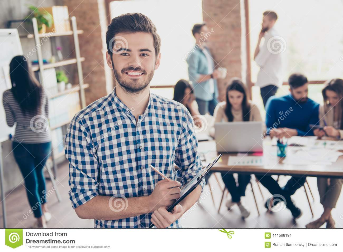 All for one and one for all! Leadership. Successful stylish young bearded man in casual checkered shirt is standing in the office