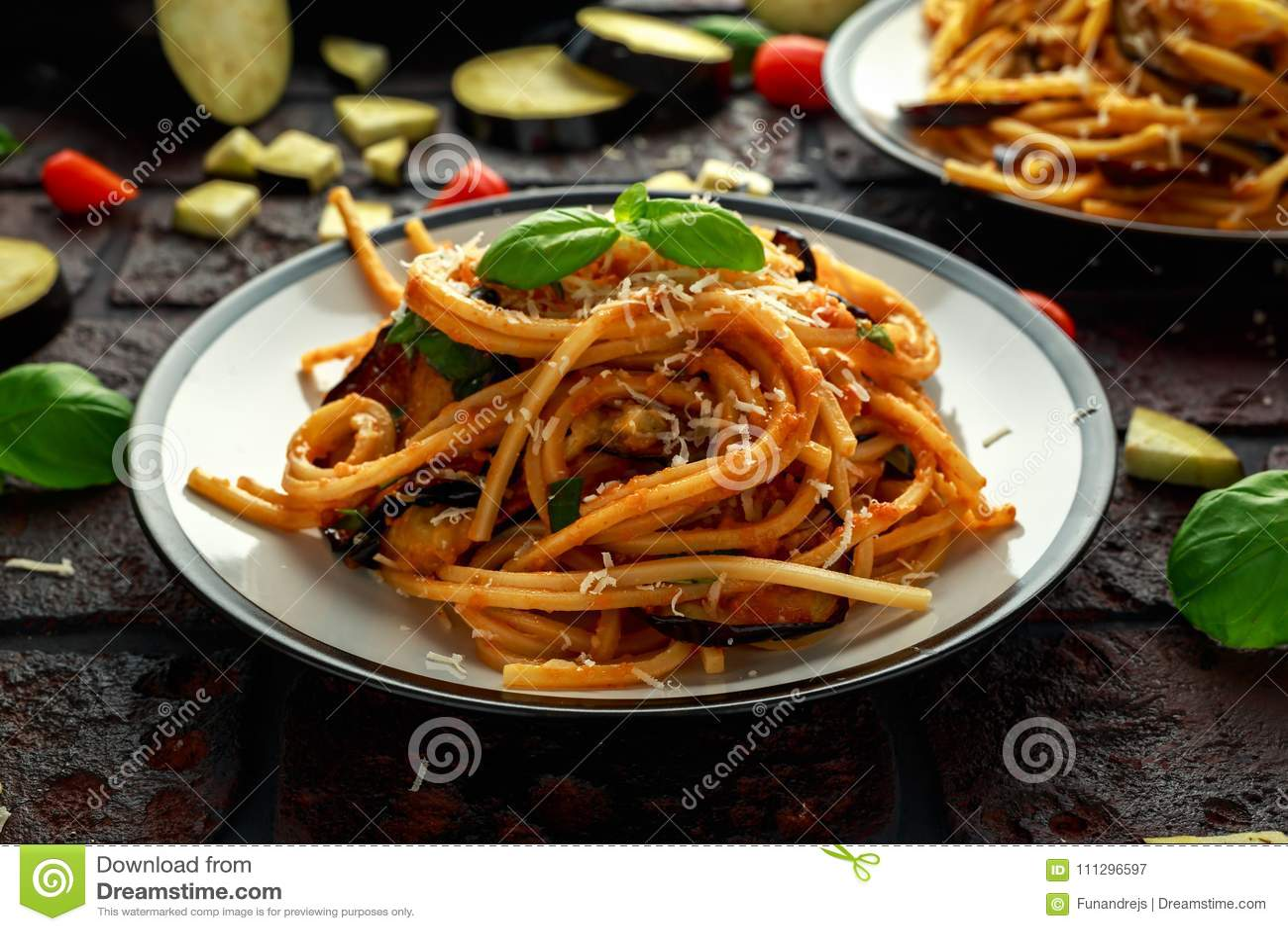 Alla italiano Norma dos espaguetes da massa do vegetariano com beringela, tomates, manjericão e queijo parmesão