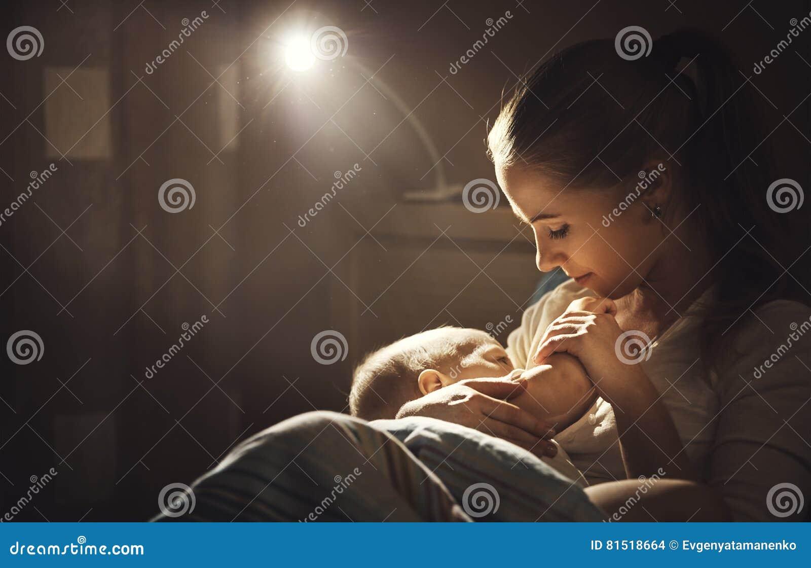 Allattamento al seno notte scura d alimentazione del seno del bambino della madre a letto