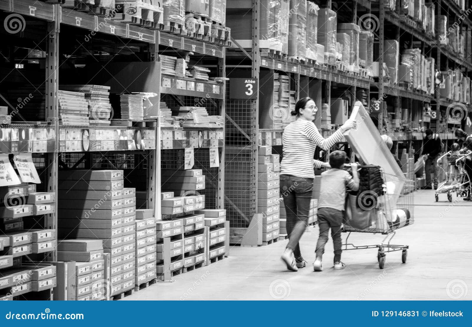 Allein erziehende Mutter-Einkaufen an IKEA-Möbelgeschäft, das Warenkorb drückt