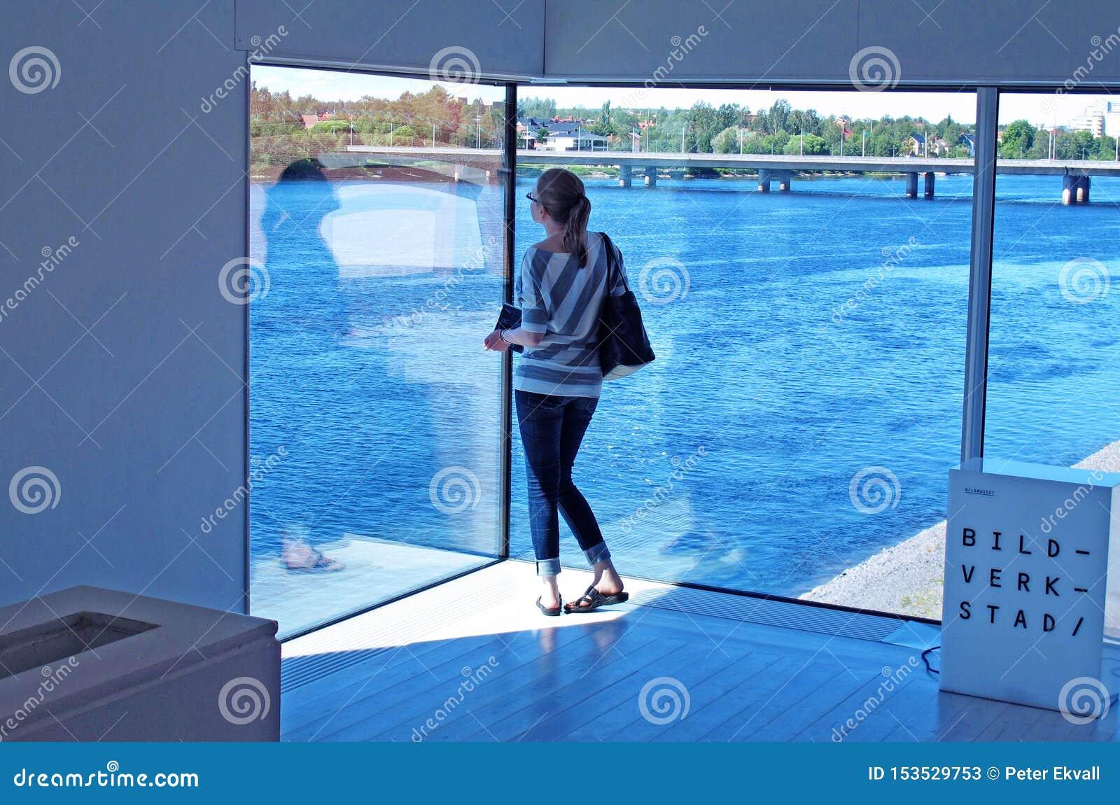 Alleinstehende Frau am Museum, das heraus Fluss und Teilen der Stadt betrachtet