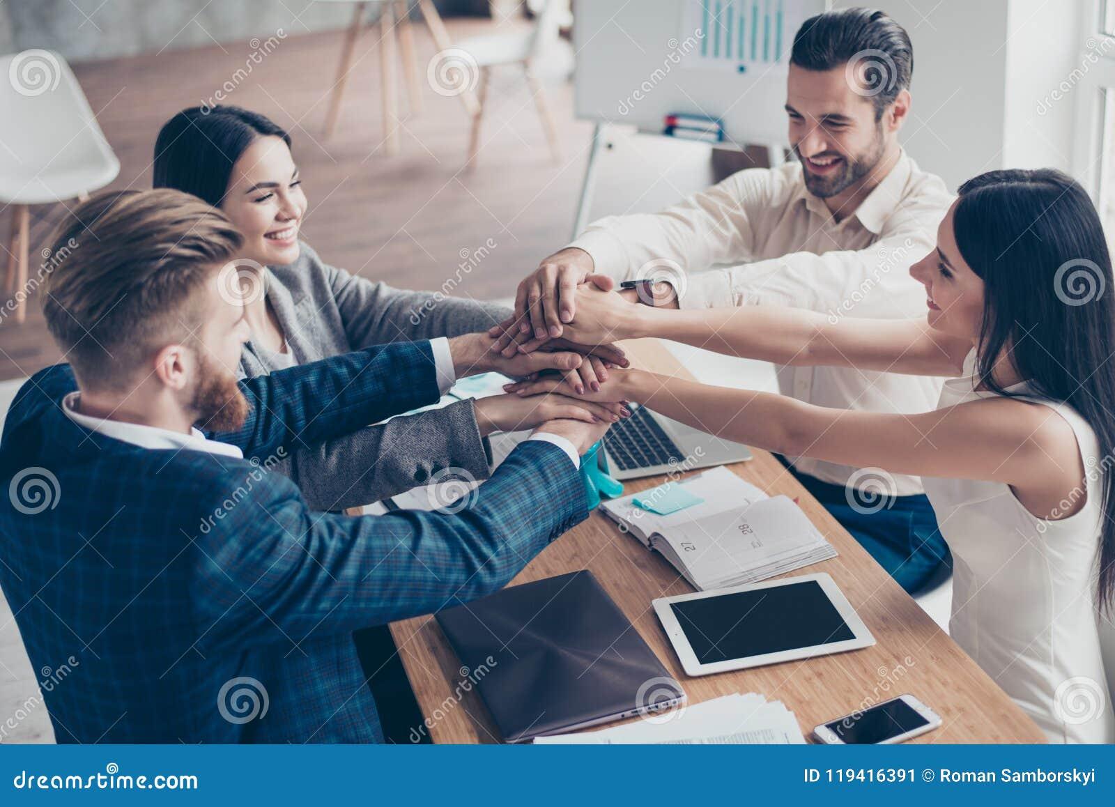 Allen samen! Gelukkig zakenlui die hun handen zetten bovenop