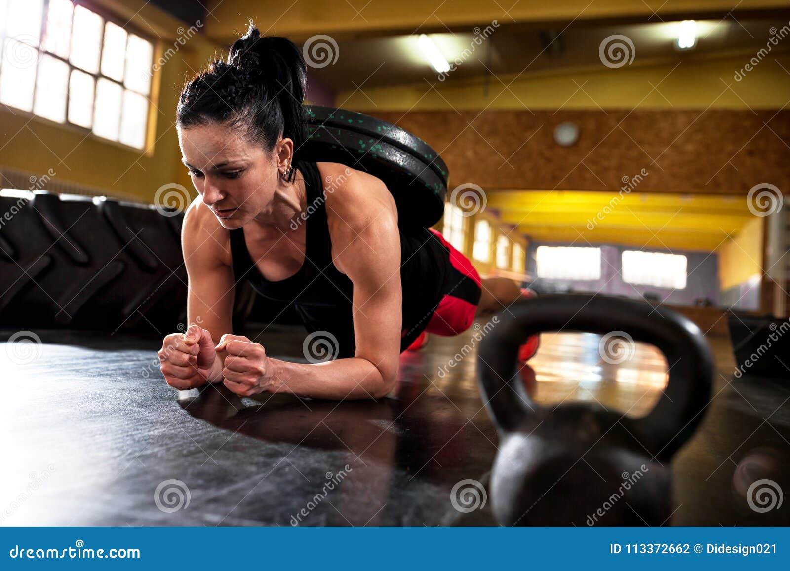 Allenamento alla palestra, facente addestramento intenso duro con il peso
