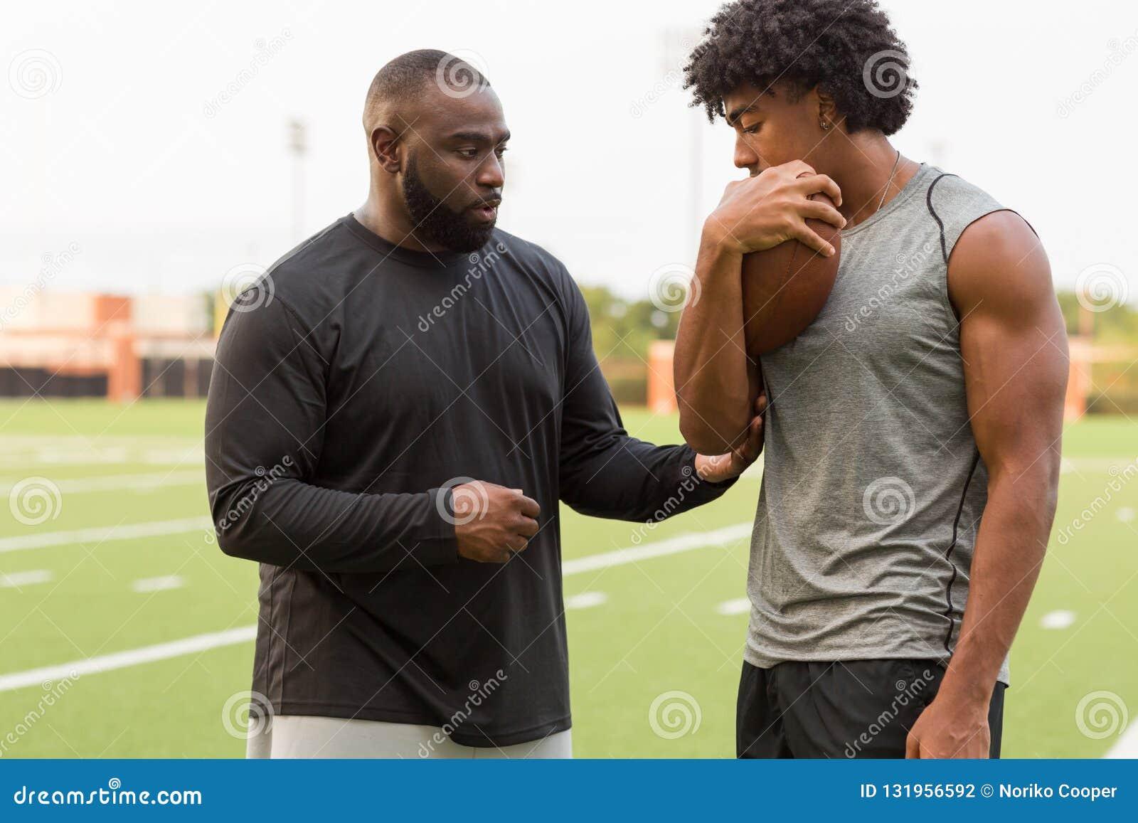 Allenatore di football americano che forma un giovane atleta