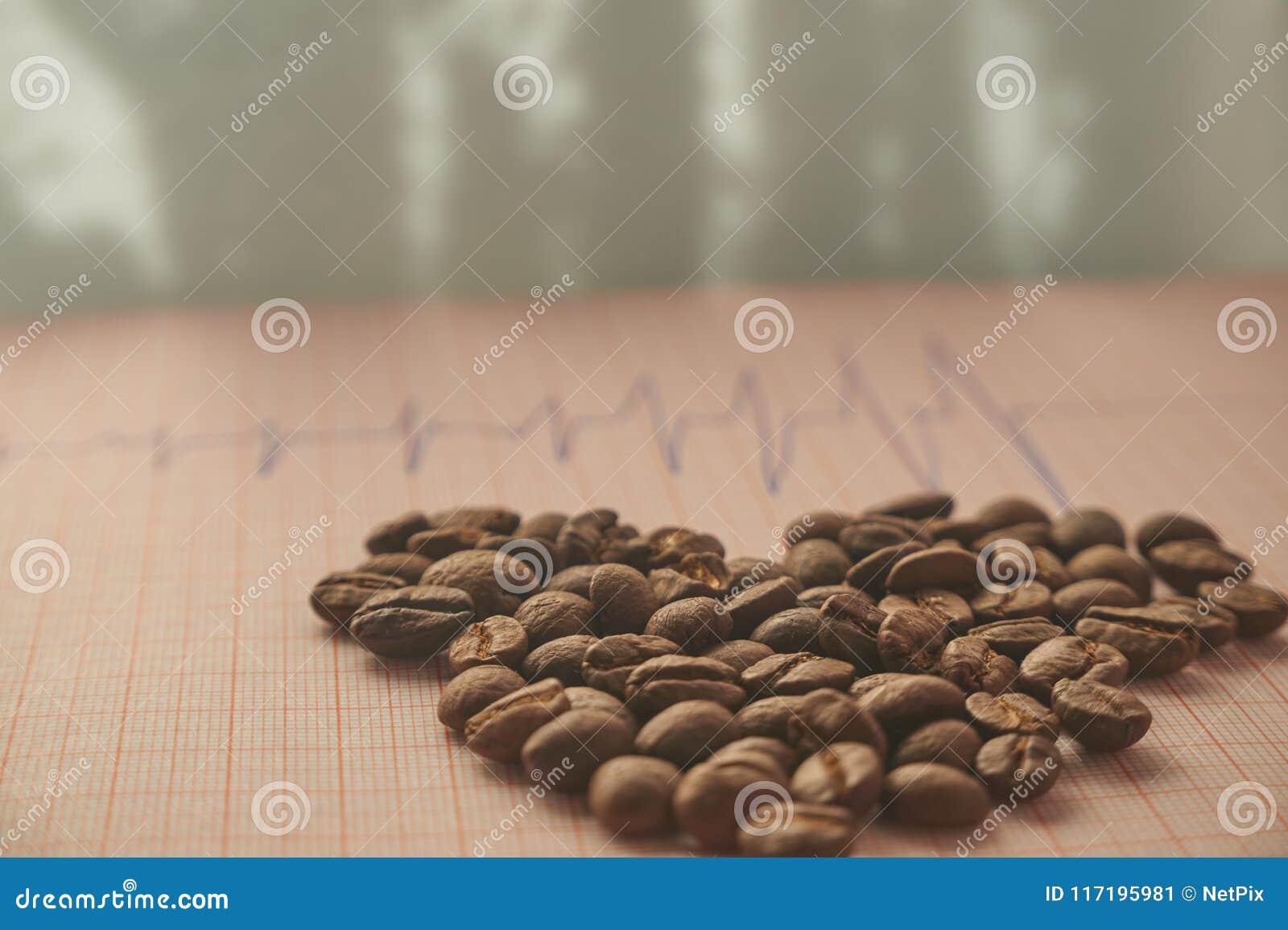 Allenti i chicchi di caffè arrostiti su un tracciato di ECG