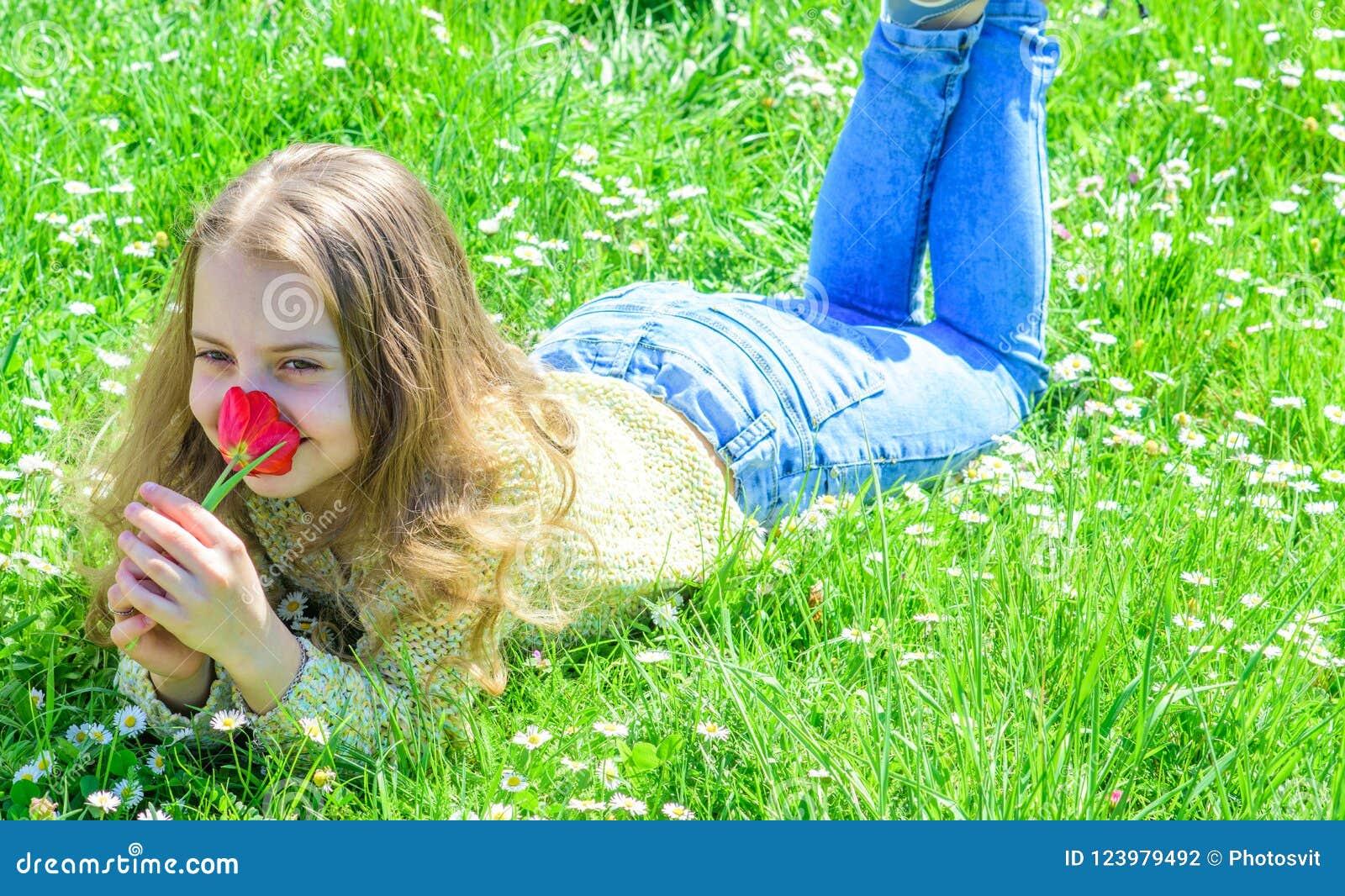 Allergiekonzept Kind genießen Duft der Tulpe beim Lügen an der Wiese Mädchen mit dem langen Haar, das auf grassplot, Gras liegt