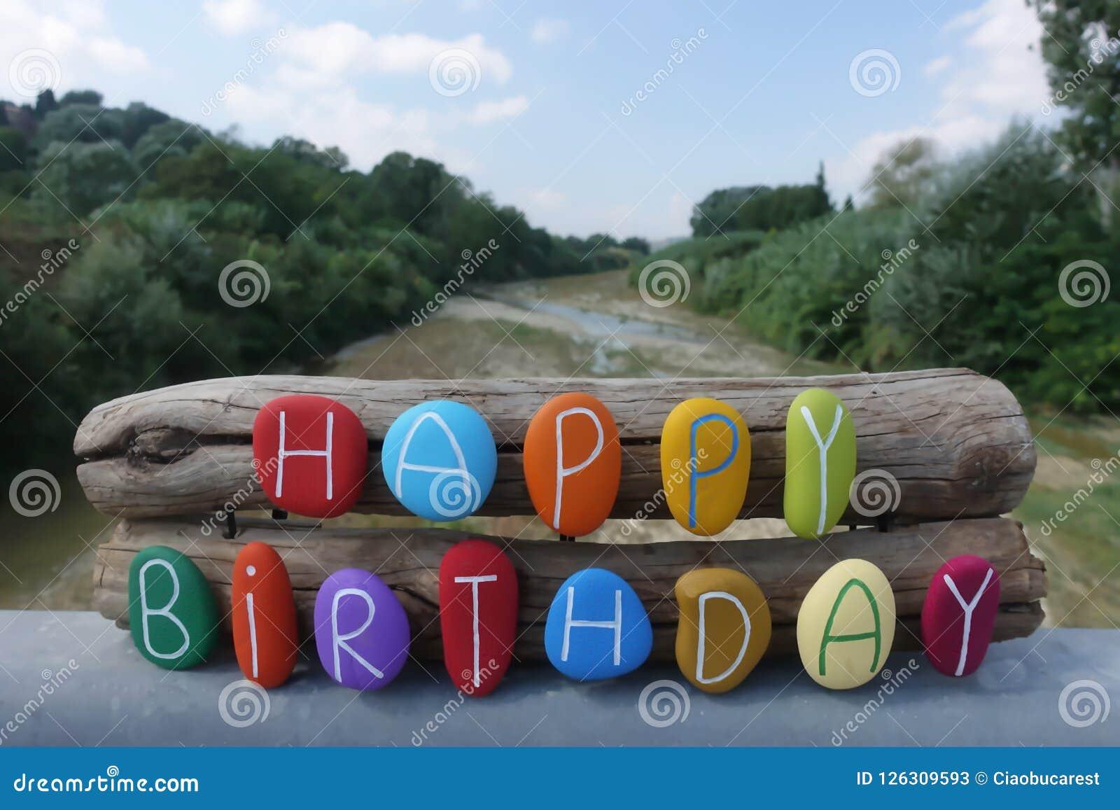 Alles- Gute zum Geburtstagtext mit farbigen Steinen über zwei hölzernen Stücken und natürlichem Hintergrund