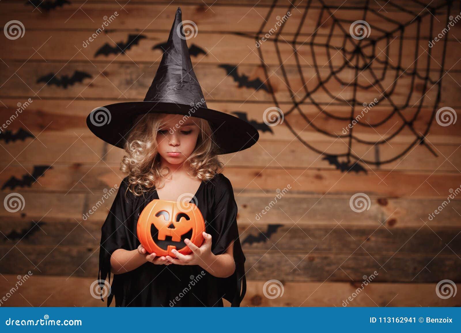 Allhelgonaaftonhäxabegrepp - litet caucasian häxabarn som sviker med ingen godis i krus för halloween godispumpa över