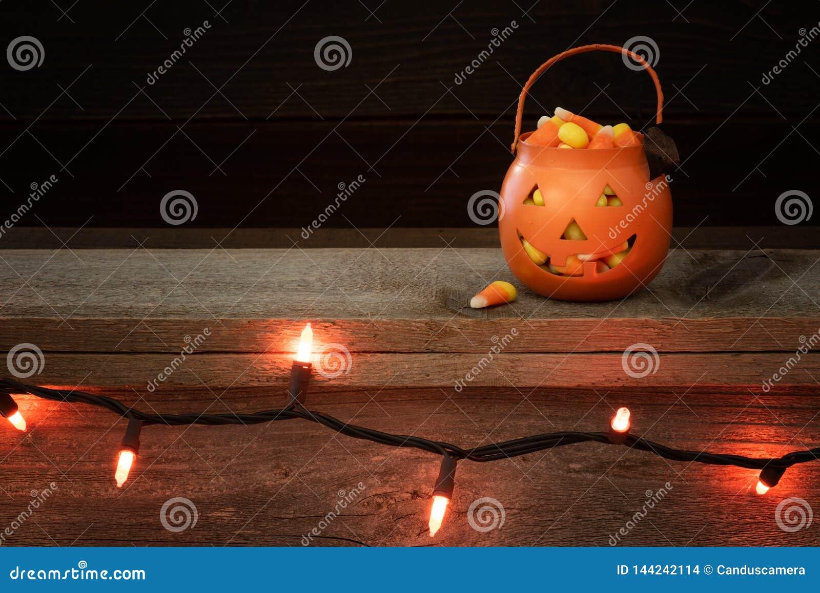 Allhelgonaaftonpumpa för litet trick som eller festfylls med godishavre på en lantlig trähylla med rad av orange ljus och mörk ba