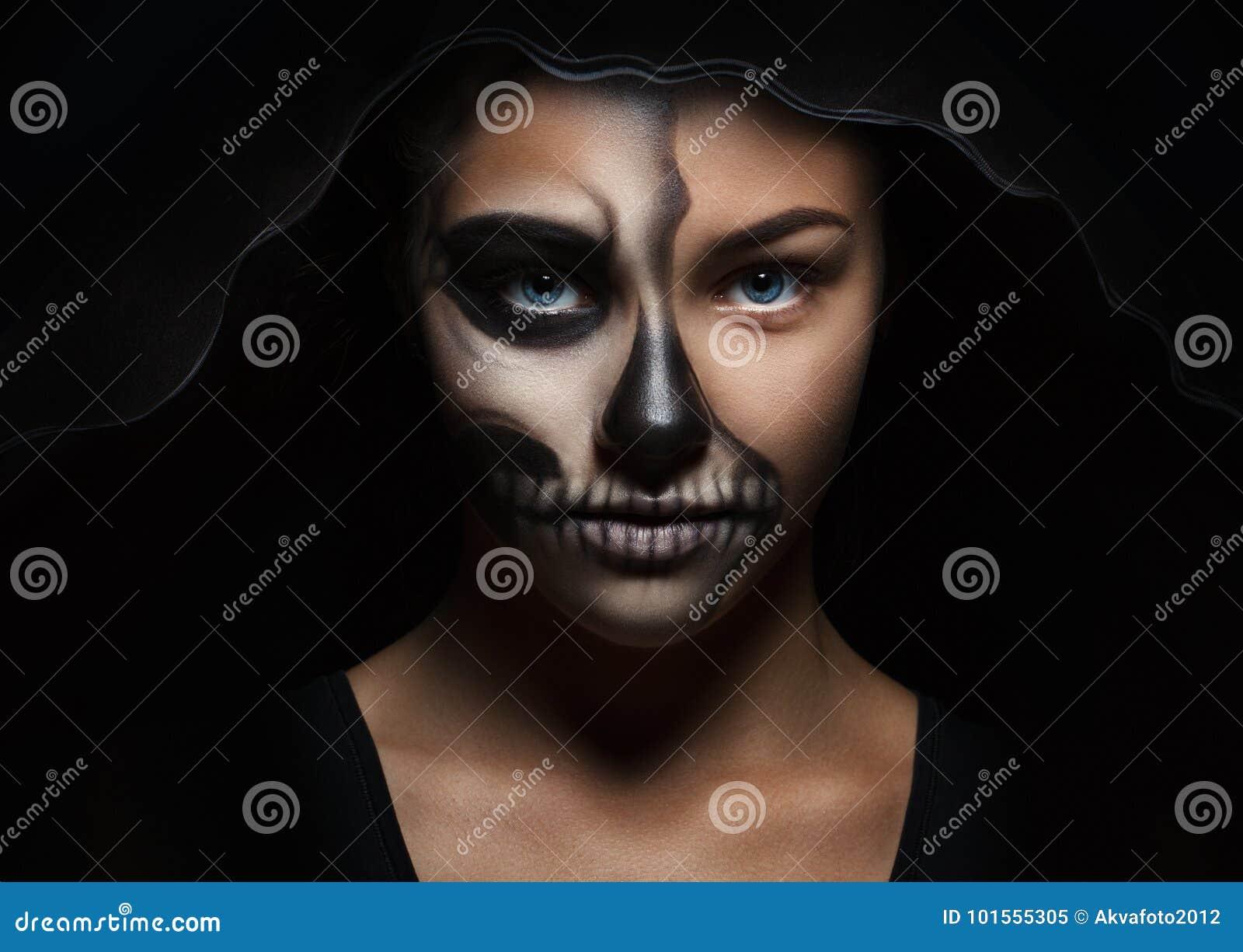 Allhelgonaaftonstående av den unga härliga flickan i en svart huv skelett- makeup
