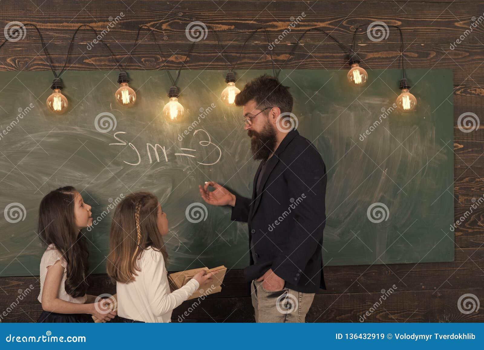 Allievi delle ragazze e dell insegnante in aula vicino alla lavagna L uomo con la barba in vestito convenzionale insegna a scolar