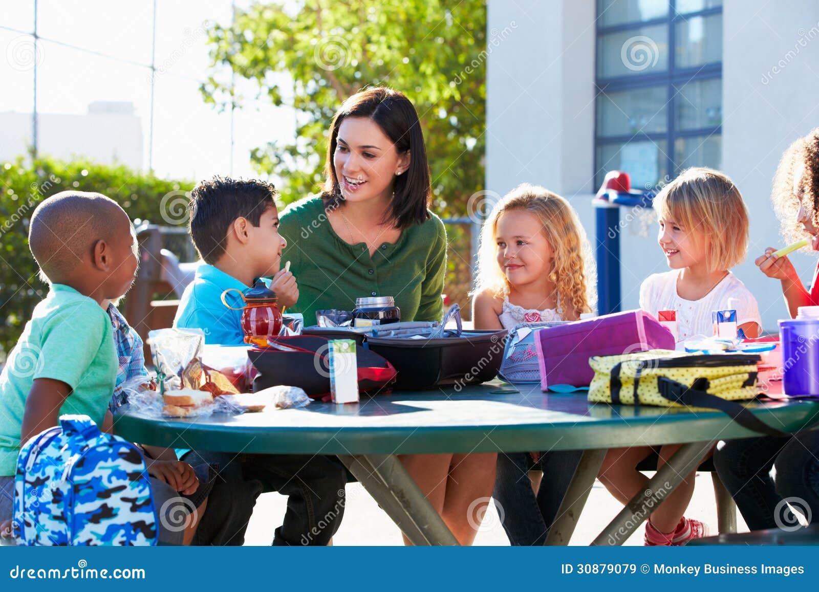 Allievi ed insegnante elementari Eating Lunch