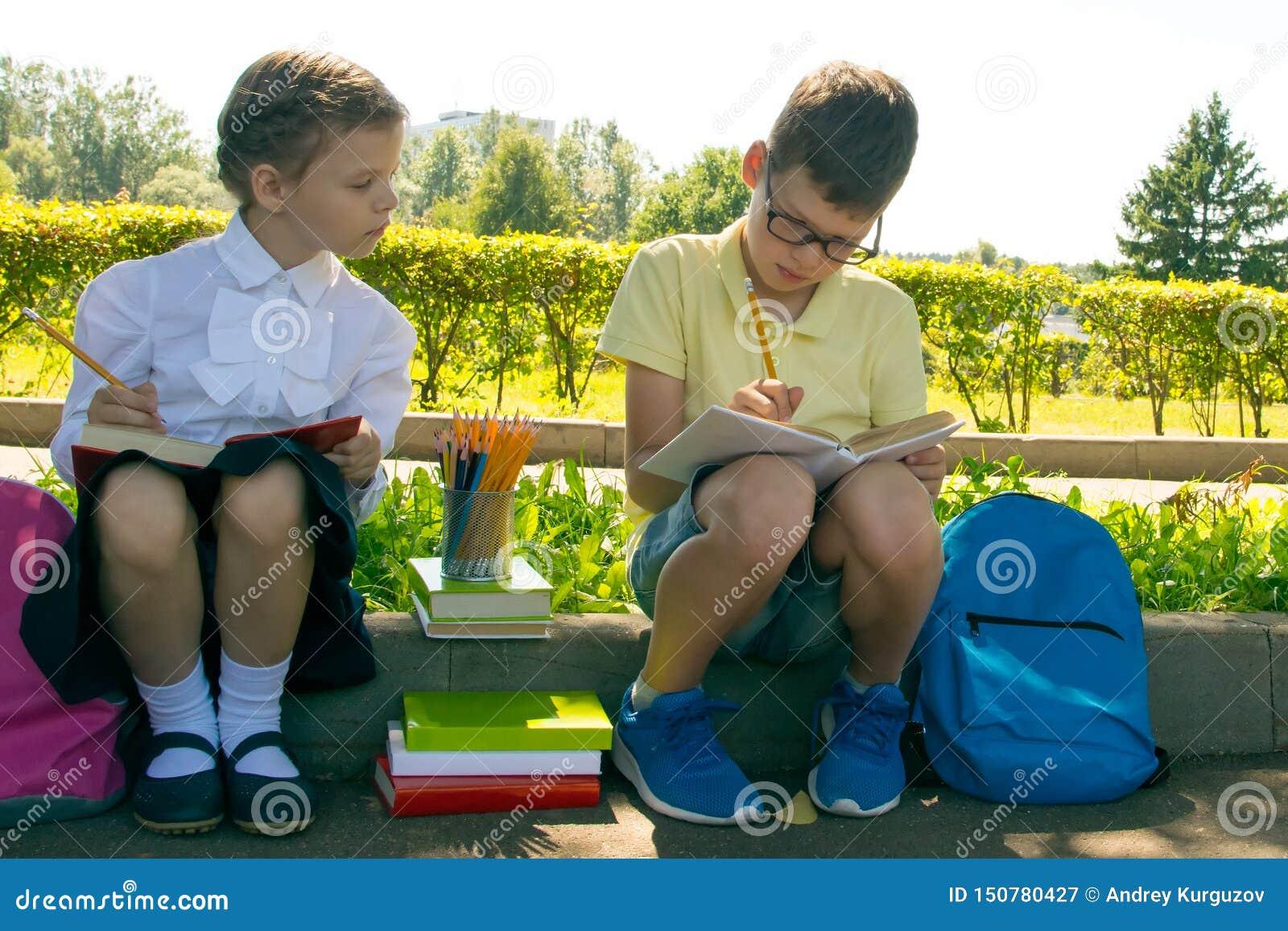 Allievi, un ragazzo e una ragazza, effettuanti le prove del programma della scuola, nel parco all aperto, tenendo le matite
