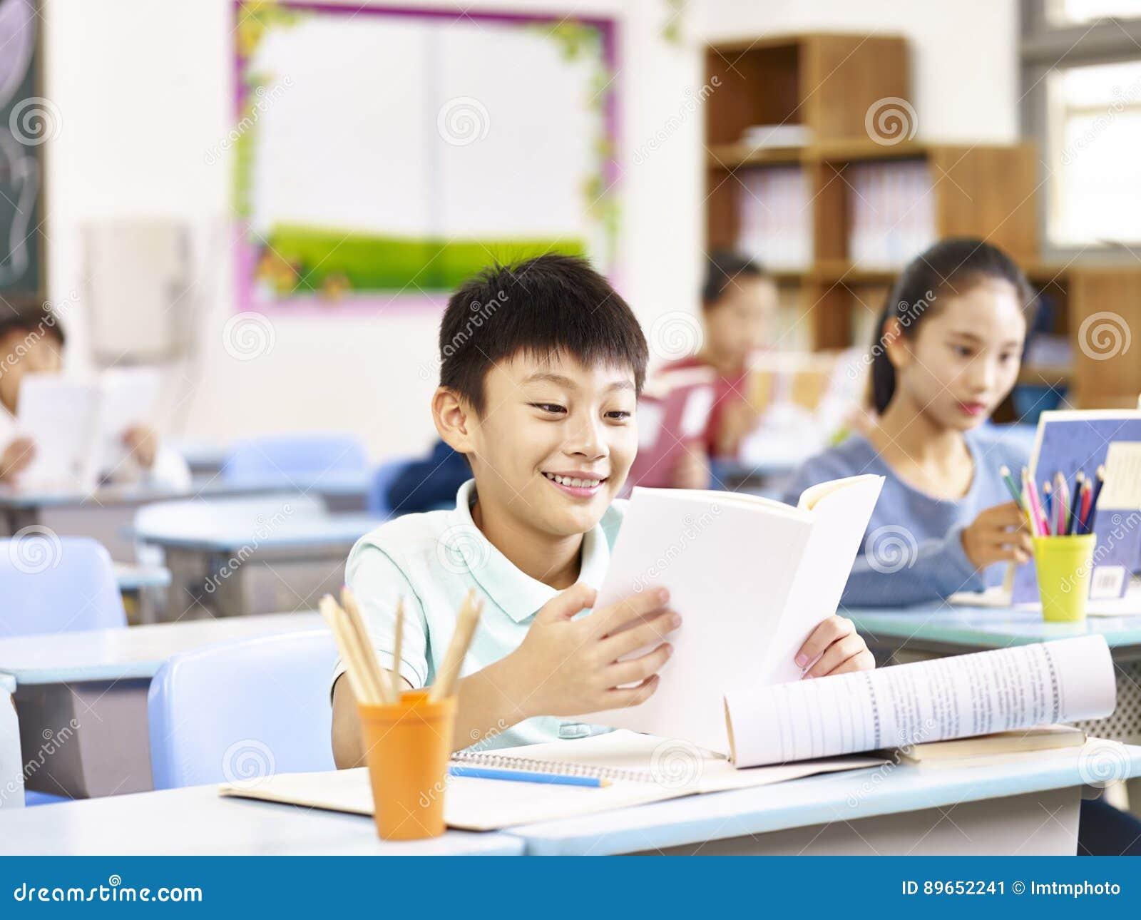 Allievo asiatico felice nella classe