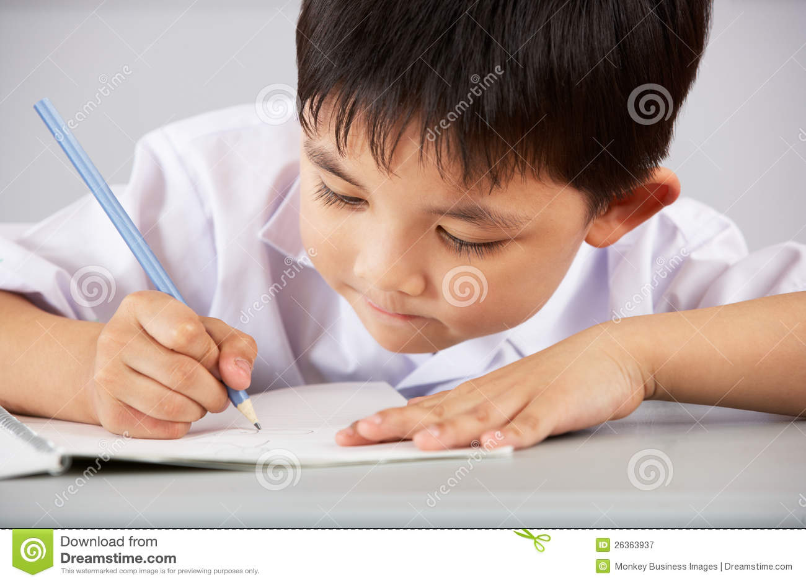 Allievo maschio che lavora allo scrittorio a scuola cinese