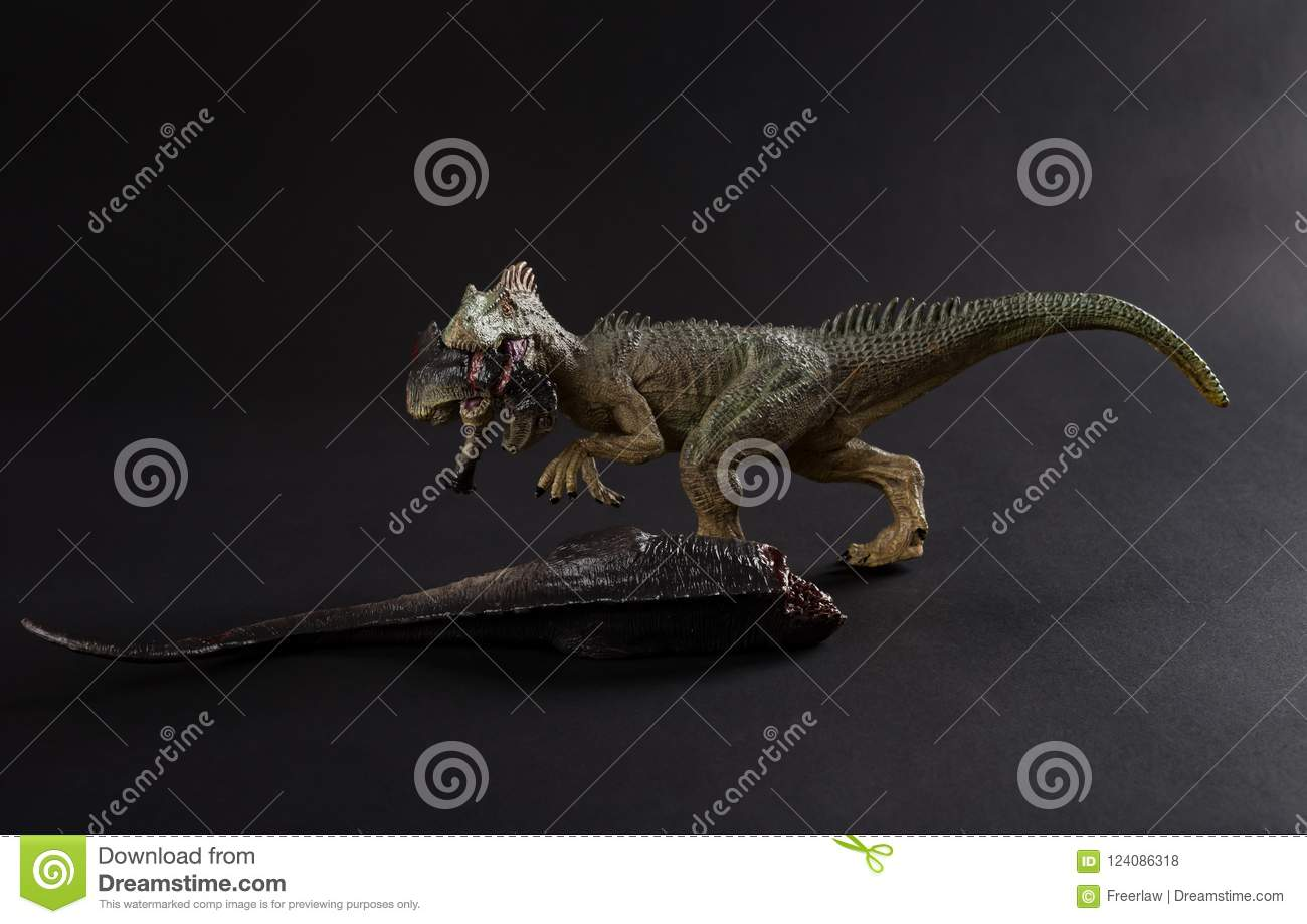 Allosaurus biting a dinosaur body on dark