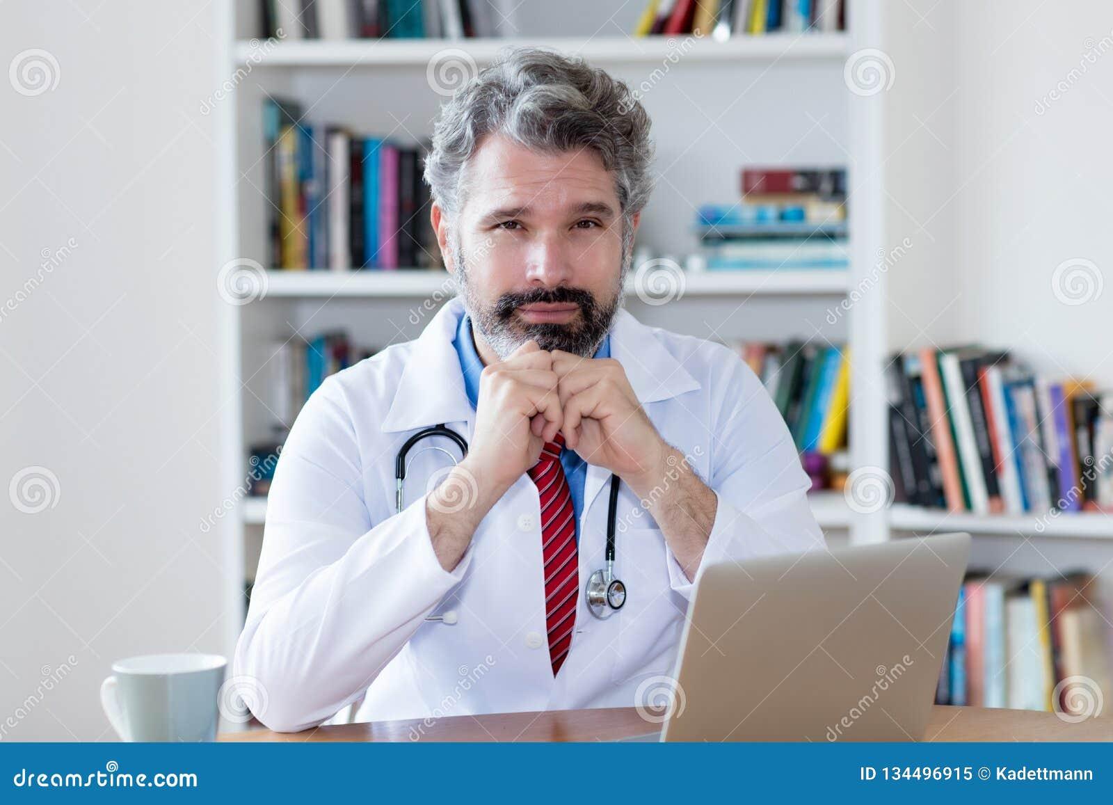 Allvarlig manlig doktor med grått hår