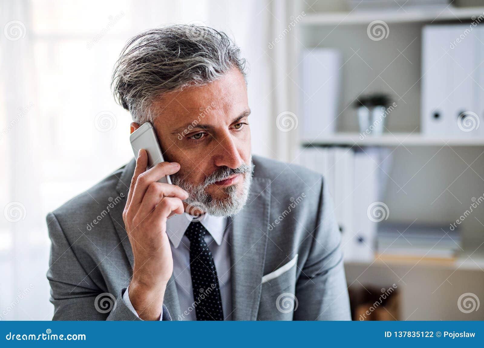 Allvarlig mogen affärsman med smartphonen som sitter på tabellen som gör en påringning