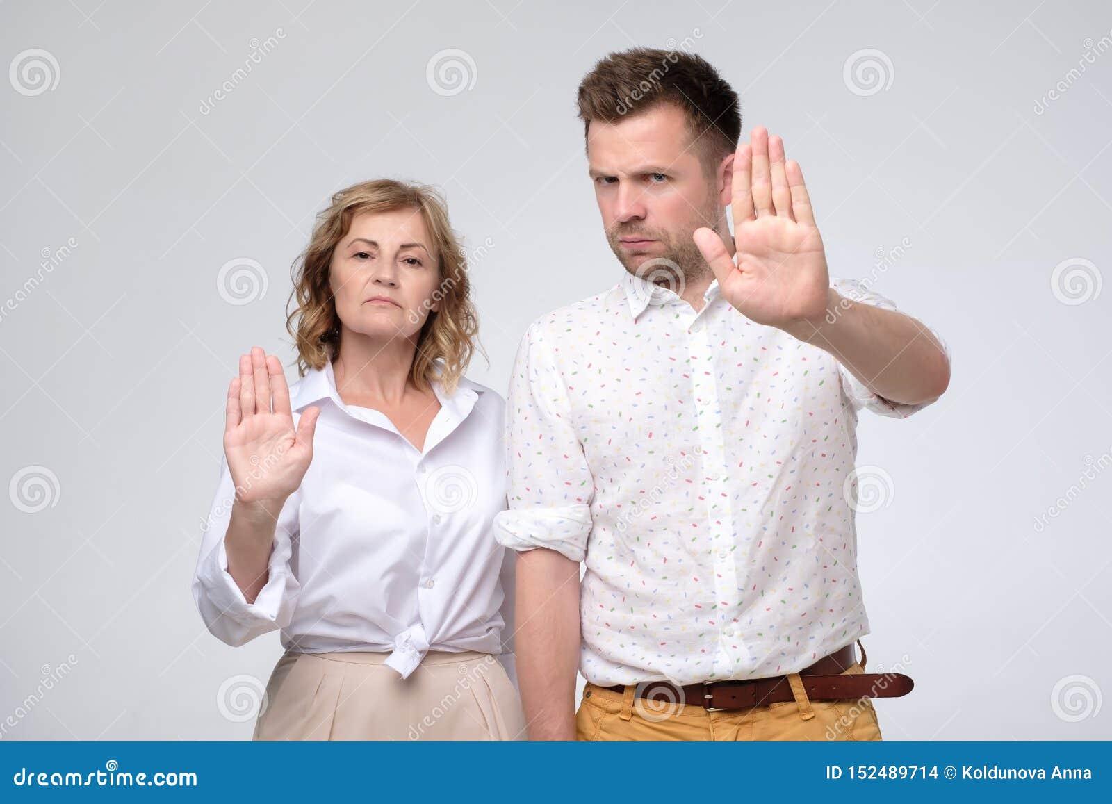 Allvarlig säker mogen man och kvinna som gör stoppgest med utsträckta armar