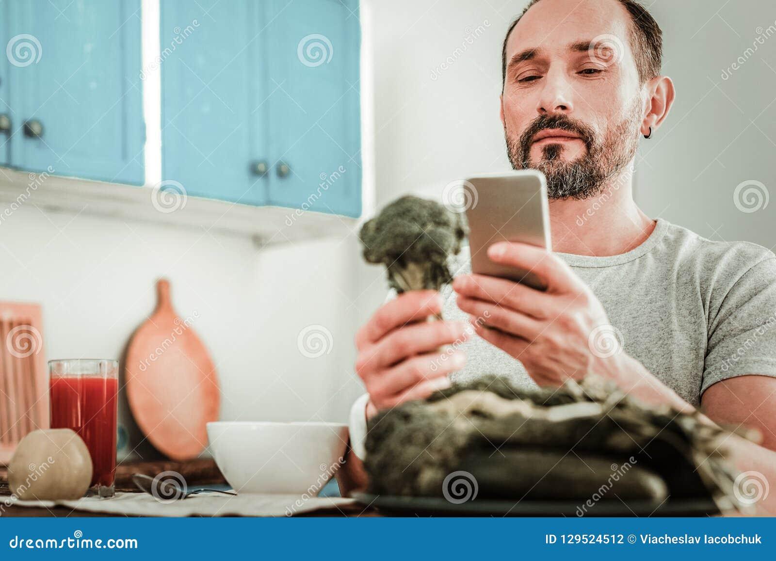Allvarlig skäggig man som ser hans smartphoneskärm