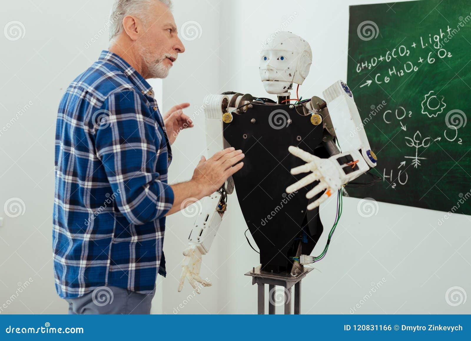 Allvarlig skäggig man som talar till roboten