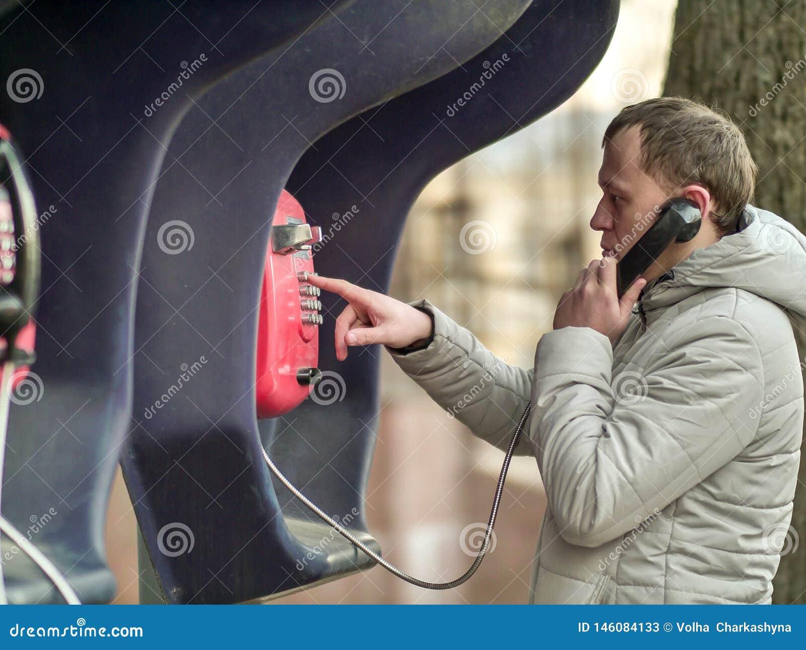 Allvarlig ung man som stannar till den röda gatapayphonen