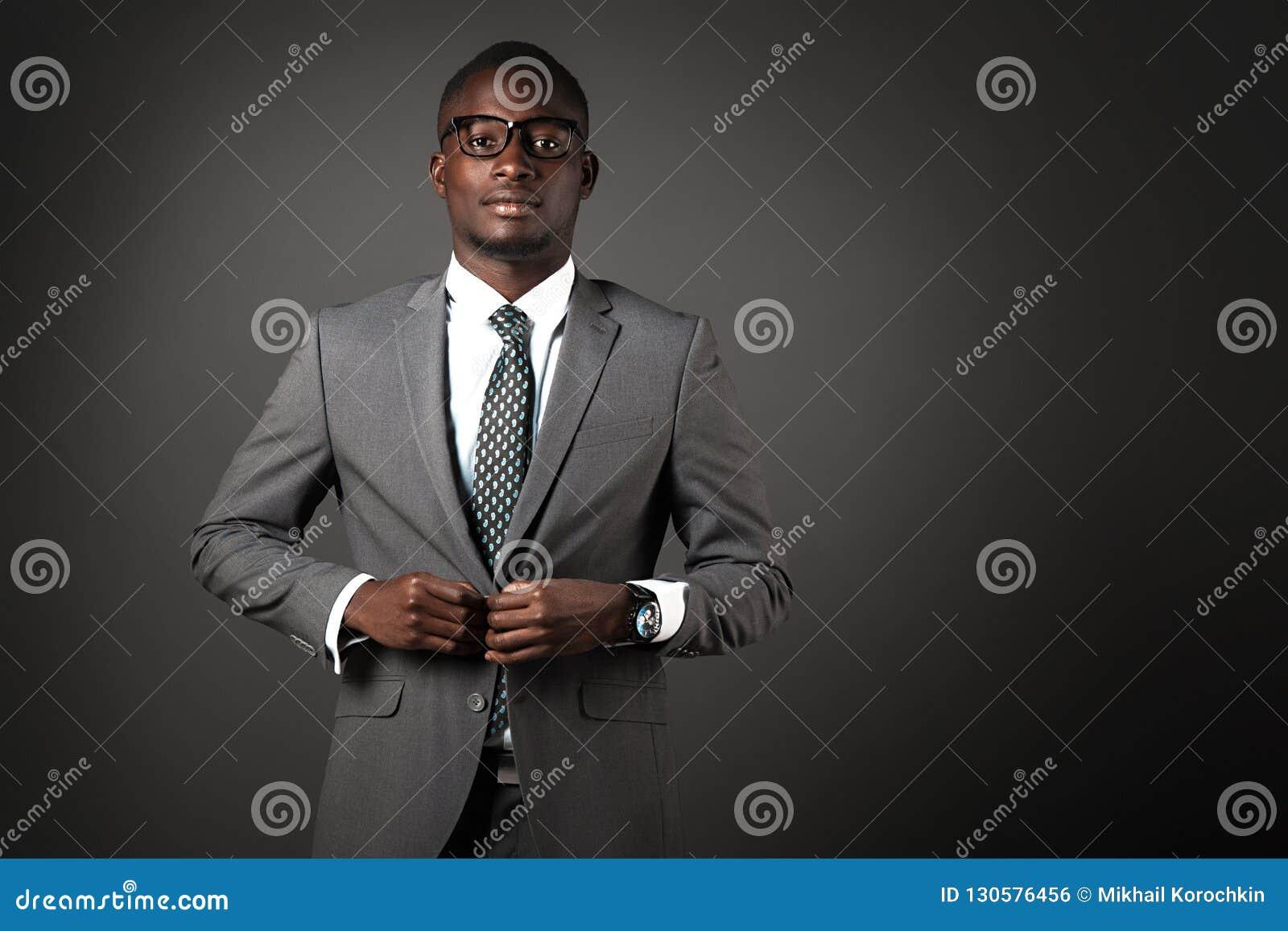 Allvarlig ung svart man med exponeringsglas och den gråa affärsdräkten