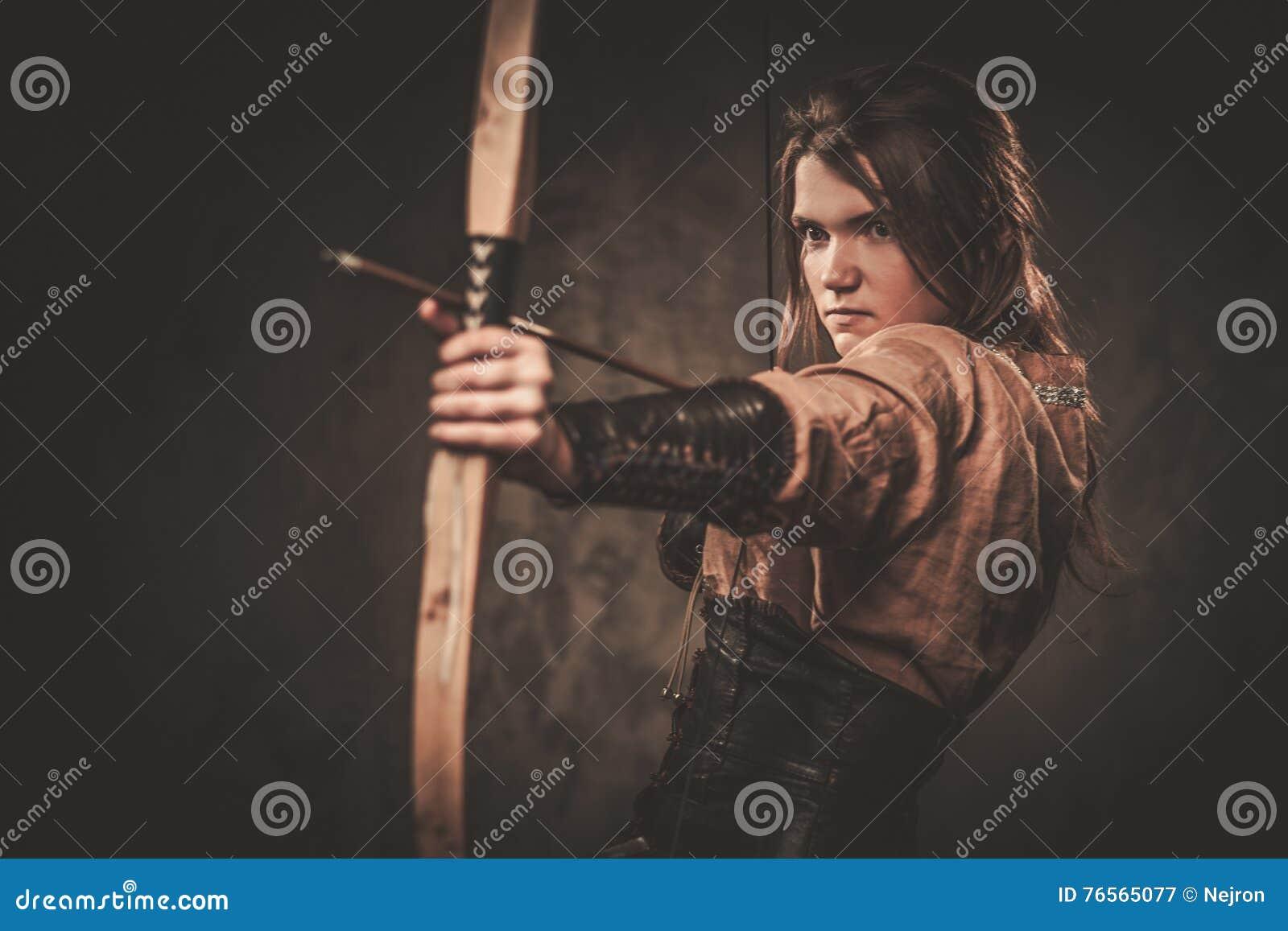 Allvarlig viking kvinna med pilbågen och pilen i traditionell kläder för en krigare som poserar på en mörk bakgrund