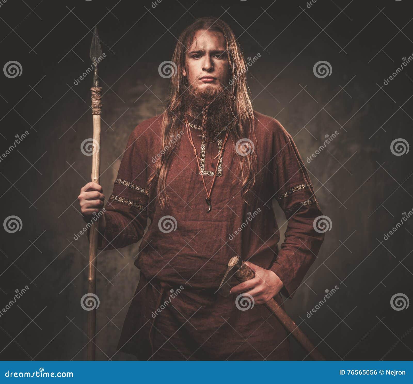 Allvarliga viking med ett spjut i traditionell kläder för en krigare som poserar på en mörk bakgrund