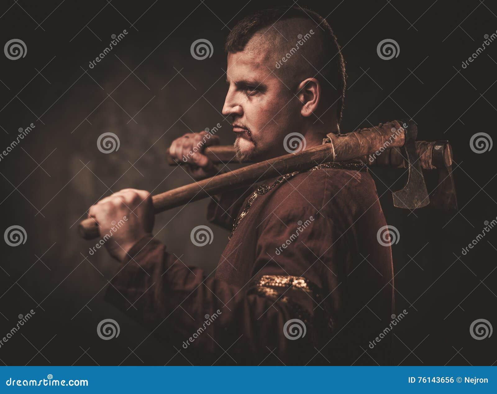 Allvarliga viking med yxa i traditionell kläder för en krigare som poserar på en mörk bakgrund