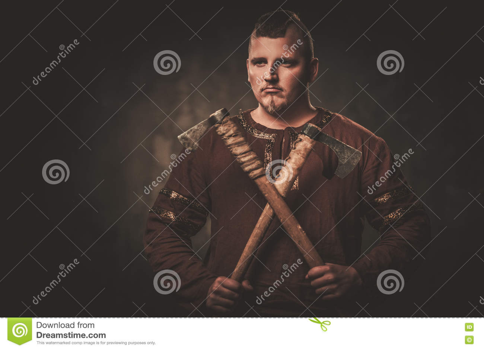 Allvarliga viking med yxor i traditionell kläder för en krigare som poserar på en mörk bakgrund