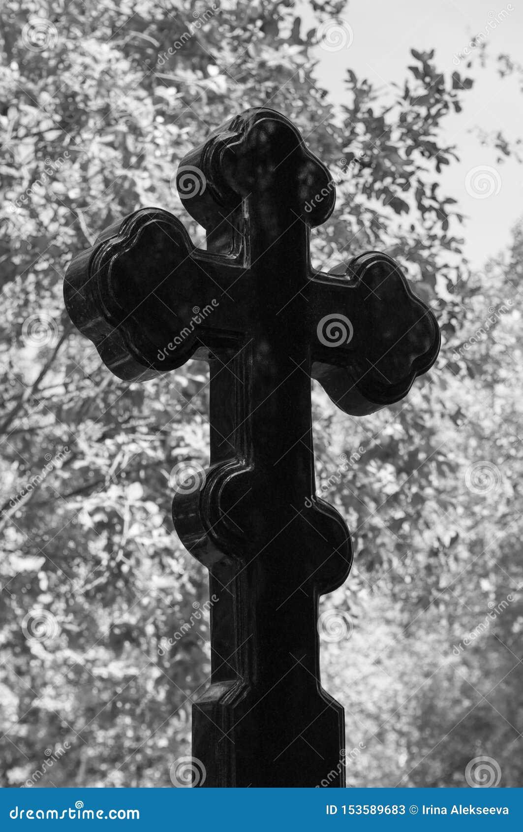 Allvarligt kors av svart granit på bakgrunden av lövverk av träd Begreppet av död, religion, tro Svartvit bild