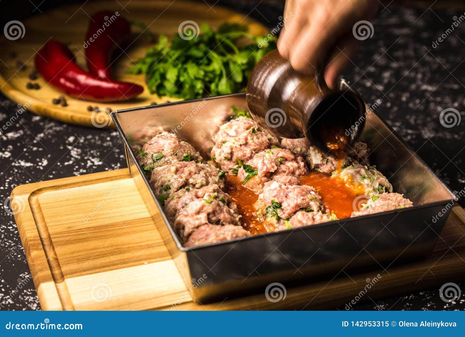 Almôndegas cruas da carne de porco no prato de cozimento metálico no molho de tomate