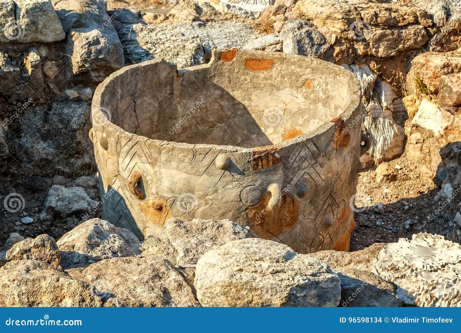 Almacenamiento antiguo antiguo del pote con el ornamento entre las piedras de las ruinas