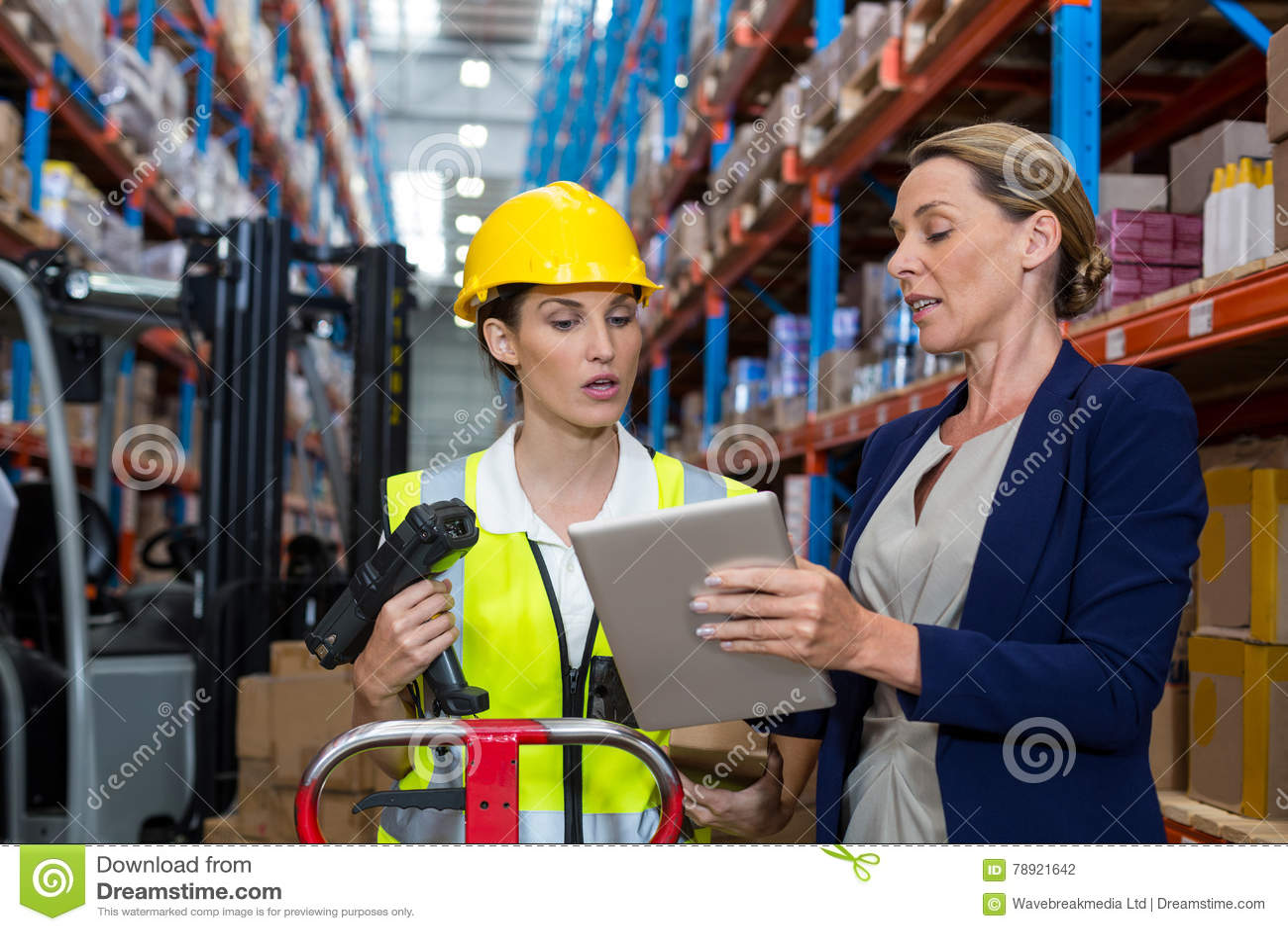 Almacene al encargado con el trabajador de sexo femenino que obra recíprocamente sobre la tableta digital