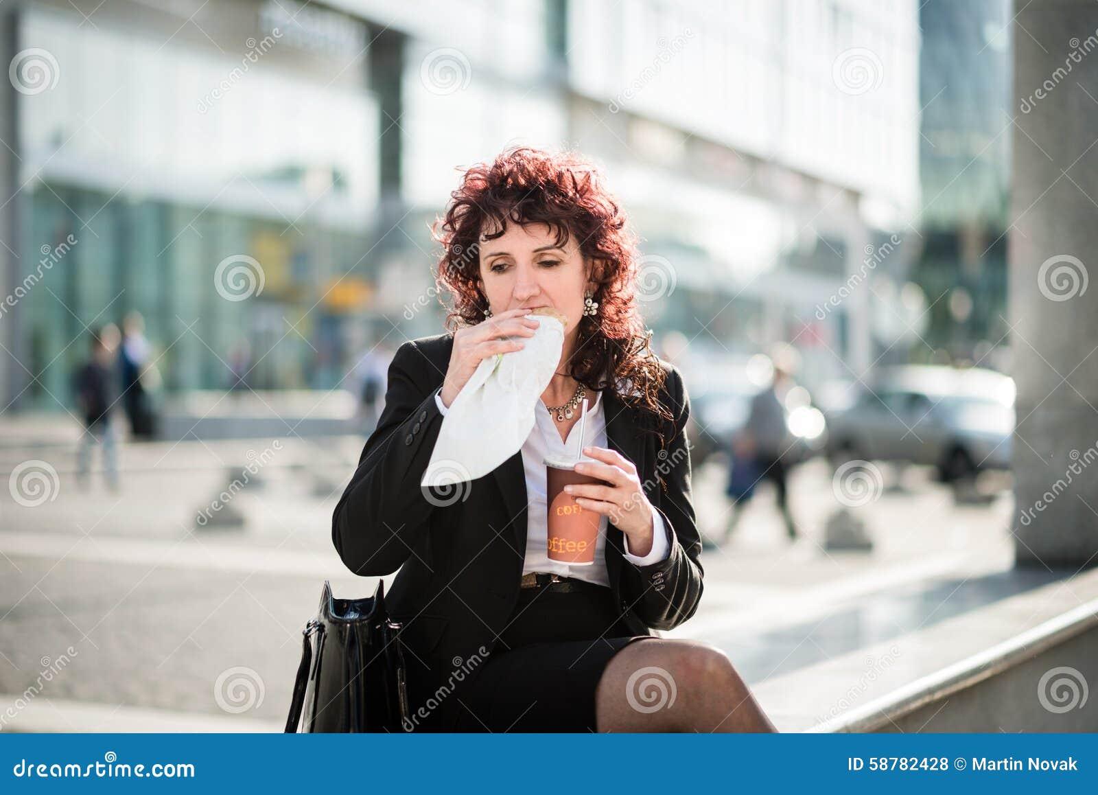 Almoço rápido - mulher de negócio que come na rua