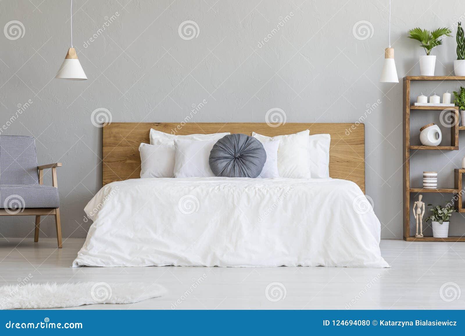 Almohada azul en la cama blanca con el cabecero de madera en interi del dormitorio
