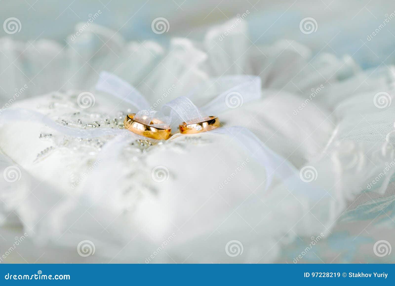 c73358e3635 Almohada blanca en forma de corazón con los anillos de oro de la boda parte  delantera