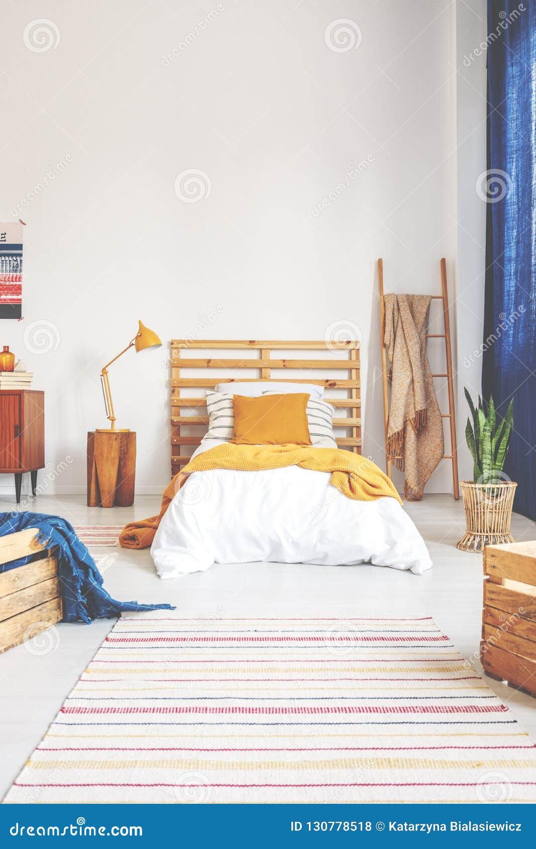 Almohada y manta amarillas en cama de madera blanca cómoda en dormitorio del adolescente con la alfombra pelada en el piso